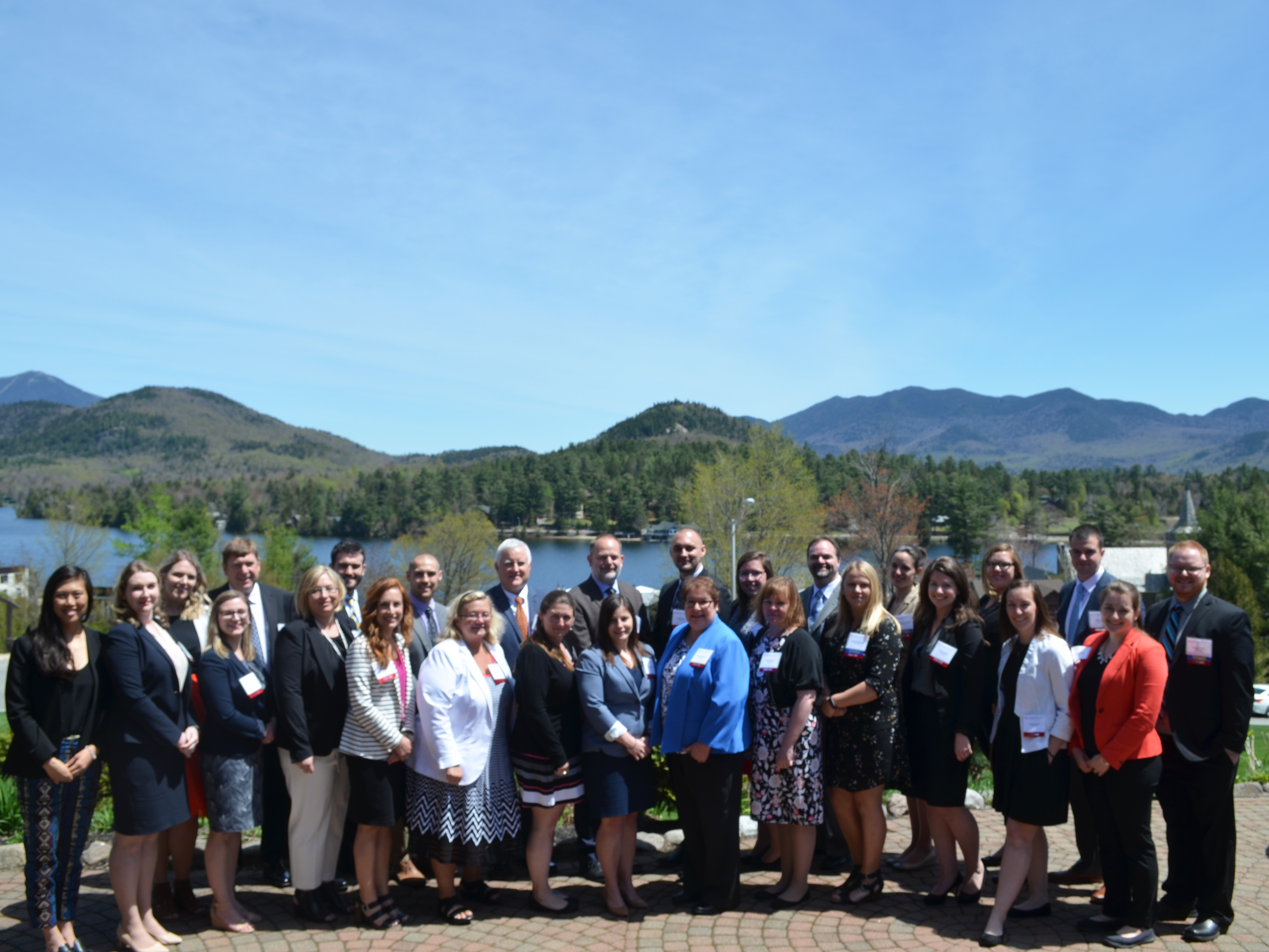 Our Atria 340B team standing in front of mirror lake and the mountains in Lake placid NY