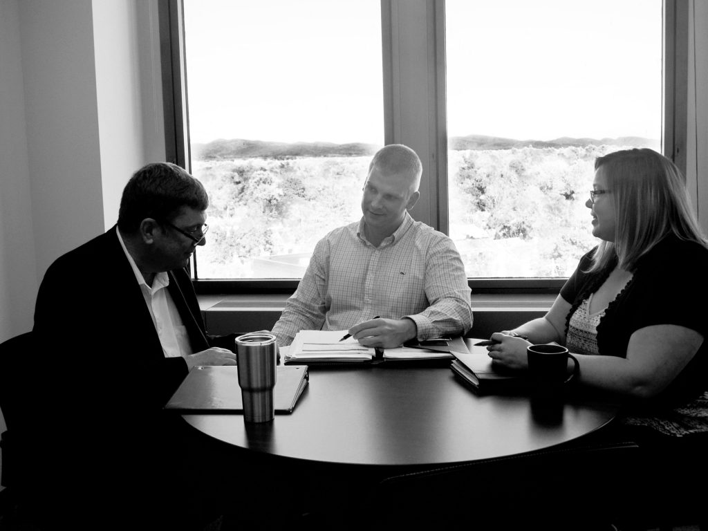 Steve, Pete, and Beth discuss a consulting project at a conference table