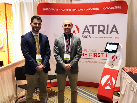 James and Andrew stand in front of the ATRIA booth at 340B Conference